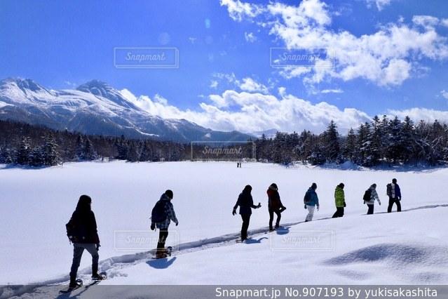 雪に覆われた斜面をスキーに乗っている人のグループ - No.907193
