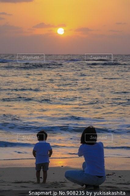 ビーチでの背景の夕日に人々 のグループの写真・画像素材[908235]