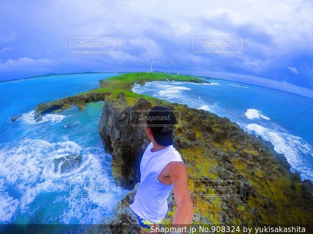 水の体の横に立っている人の写真・画像素材[908324]