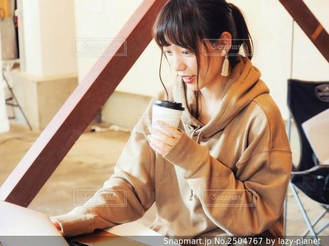 カフェでコーヒー飲みながら仕事する女性の写真・画像素材[2504767]