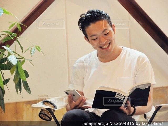 スマホを片手に笑顔で読書する男性の写真・画像素材[2504815]