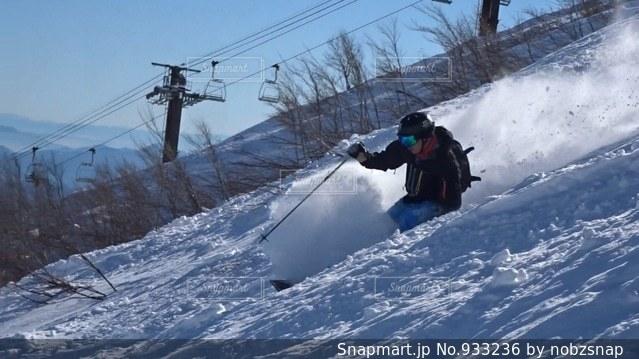 雪をスノーボードに乗る男覆われた斜面の写真・画像素材[933236]