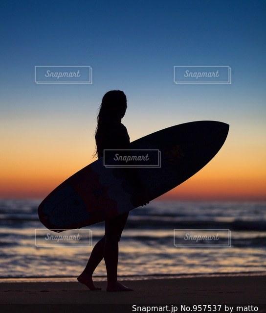 ビーチの上を歩くサーフボードを運ぶ男の写真・画像素材[957537]