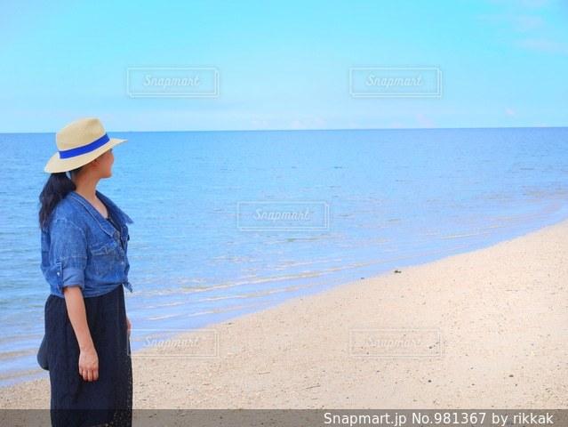 水の体の近くのビーチに立っている人の写真・画像素材[981367]