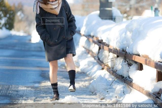 道に積もった雪で遊ぶ女子高生の写真・画像素材[1841586]