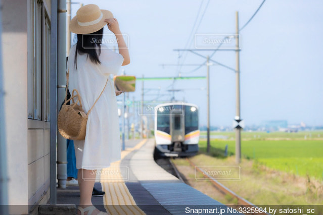 ローカル線のホームで電車を待つワンピース姿の女性の写真・画像素材[3325984]