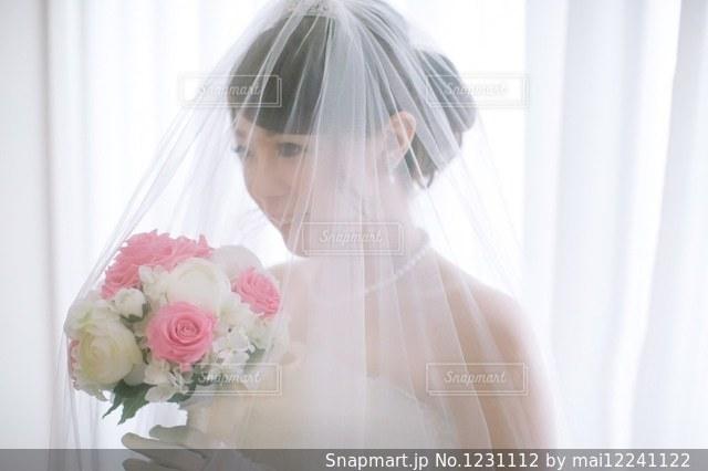 窓の前でウェディング ドレスの人の写真・画像素材[1231112]