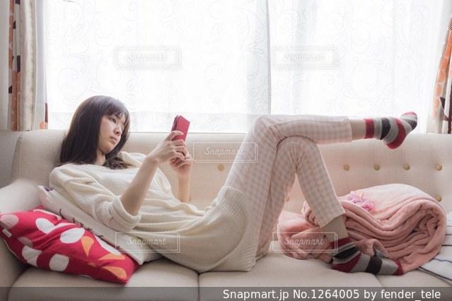 ベッドの上で横になっている女性の写真・画像素材[1264005]