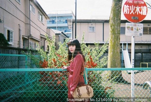 フェンスの前で看板を持っている人の写真・画像素材[1234039]