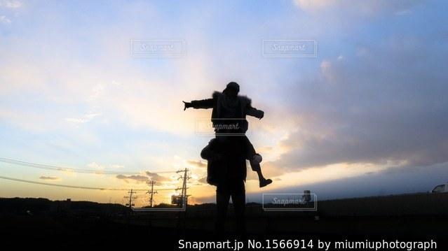 バック グラウンドで夕日を持つ人の写真・画像素材[1566914]