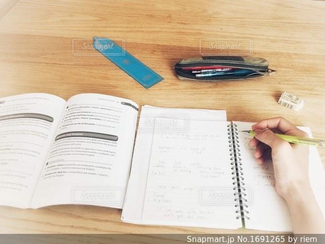 木製テーブルの上に座っている本の写真・画像素材[1691265]