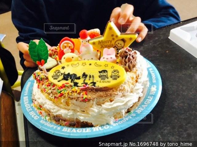 ケーキでテーブルに座っている人の写真・画像素材[1696748]