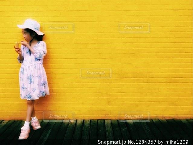 黄色い壁と女の子の写真・画像素材[1284357]