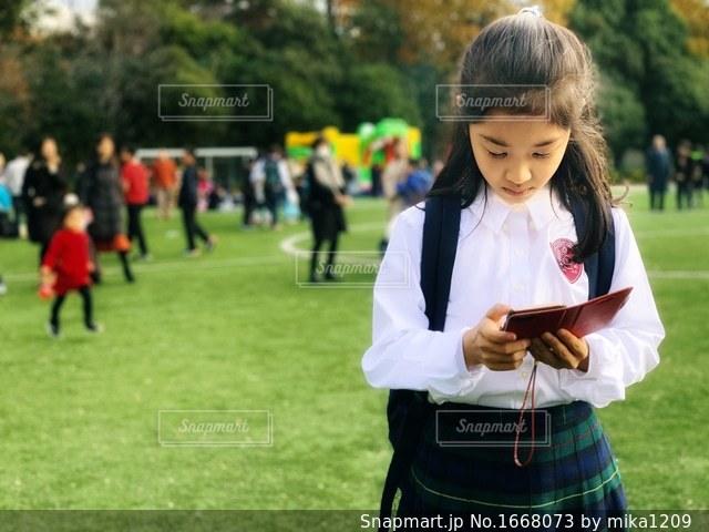 校庭でスマホチェックする少女の写真・画像素材[1668073]