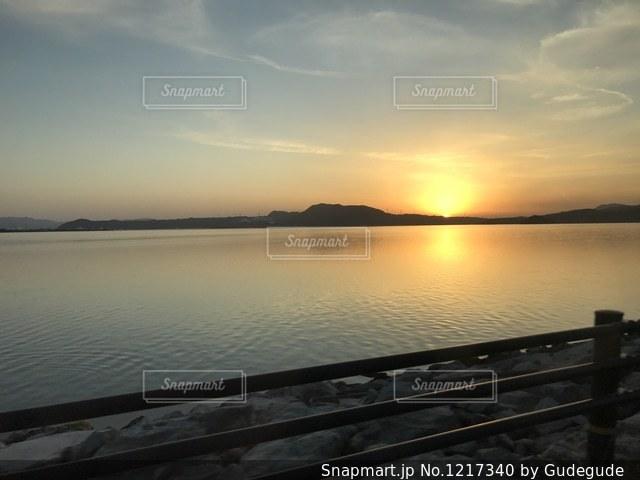 水の体の横にあるベンチの写真・画像素材[1217340]