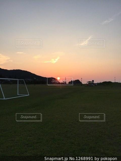 芝生のフィールドに沈む夕日の写真・画像素材[1268991]