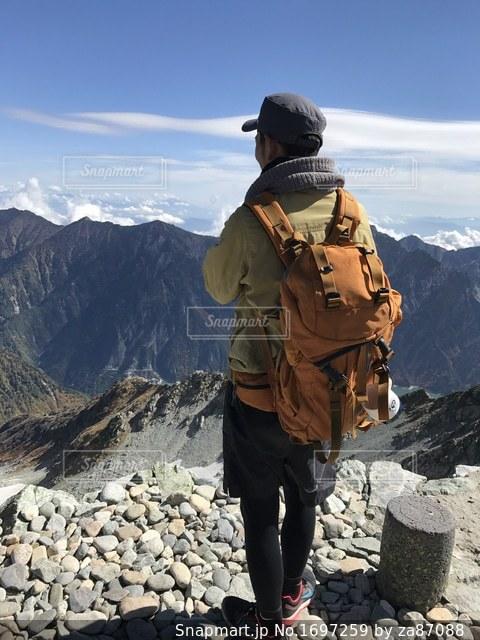 山の前に立っている男の写真・画像素材[1697259]