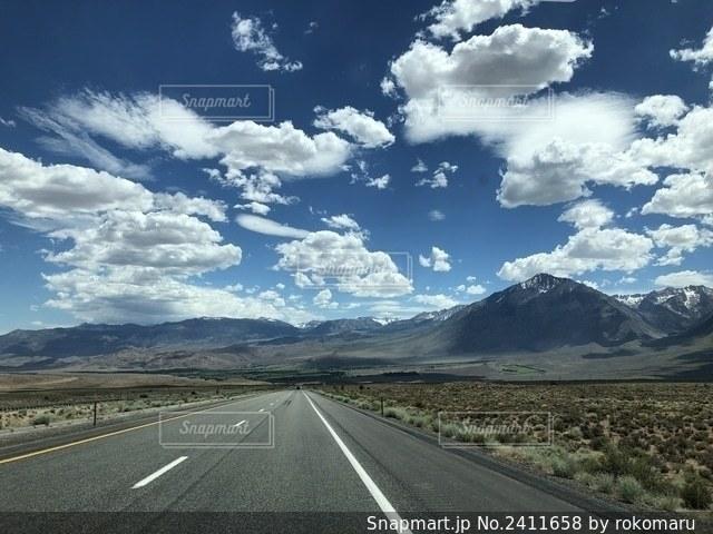 山を背景にした空の道の写真・画像素材[2411658]