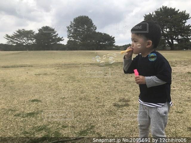 草の上に立っている小さな男の子の写真・画像素材[2095691]