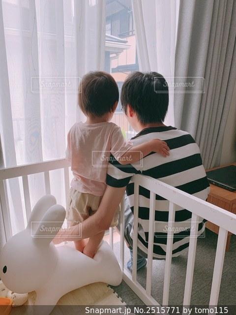 カーテンの前の椅子に座っている少年の写真・画像素材[2515771]