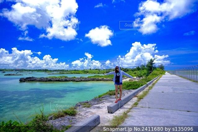 水域の隣に立っている人の写真・画像素材[2411680]