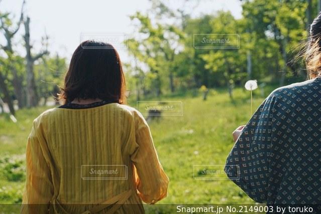 タンポポの綿毛を持って歩く女性の写真・画像素材[2149003]