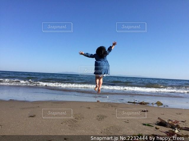 浜辺で空を飛んでいる女の子の写真・画像素材[2232444]