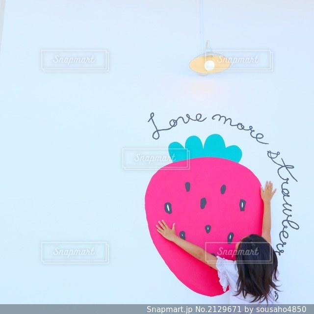 壁のいちごのイラストに抱きつく女の子の写真・画像素材[2129671]