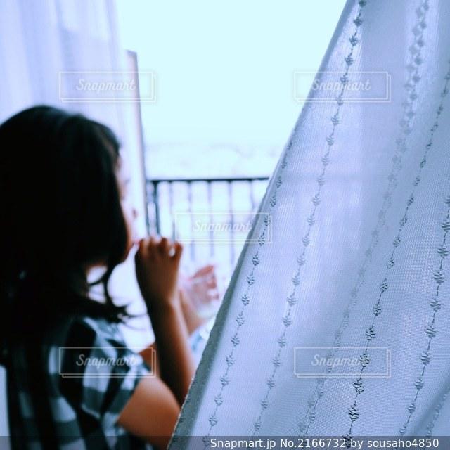 レースのカーテン越しにシャボン玉を吹く女の子の写真・画像素材[2166732]