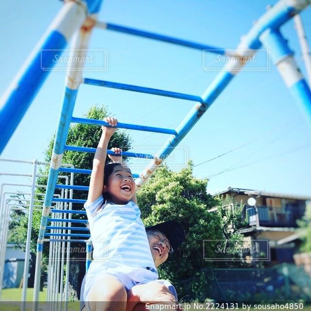 屋外でうんていする娘を支える父親の写真・画像素材[2224131]