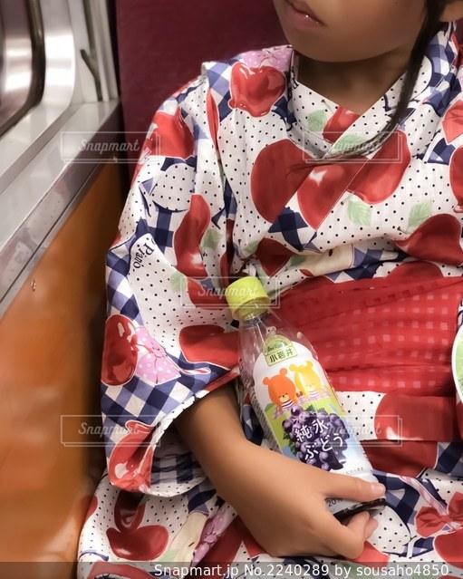 電車内で浴衣を着てジュースを抱える女の子の写真・画像素材[2240289]
