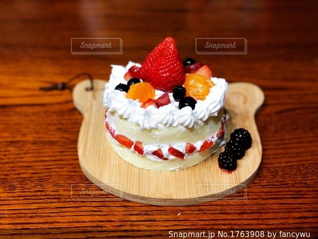 木製テーブルの上に座っているケーキの写真・画像素材[1763908]