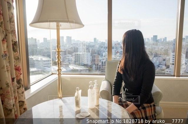 窓の前に座っている女性の写真・画像素材[1828718]