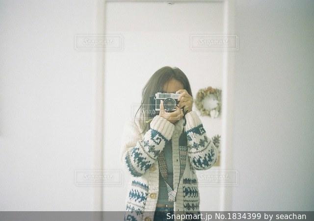 カメラにポーズ鏡の前に立っている人の写真・画像素材[1834399]