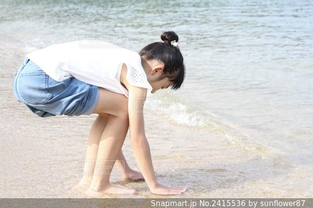 浜辺に立っている少年の写真・画像素材[2415536]