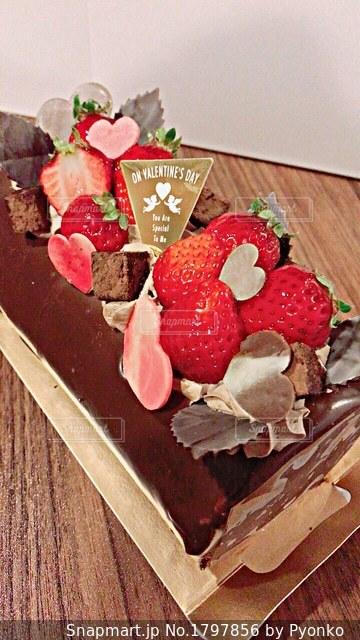 木製テーブルの上に座っているケーキの写真・画像素材[1797856]