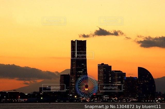 バック グラウンドで市と水体に沈む夕日の写真・画像素材[1304872]