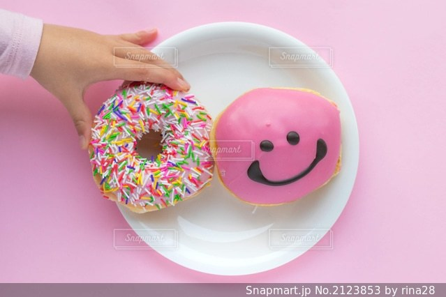 ピンクのドーナツを持つ手の写真・画像素材[2123853]