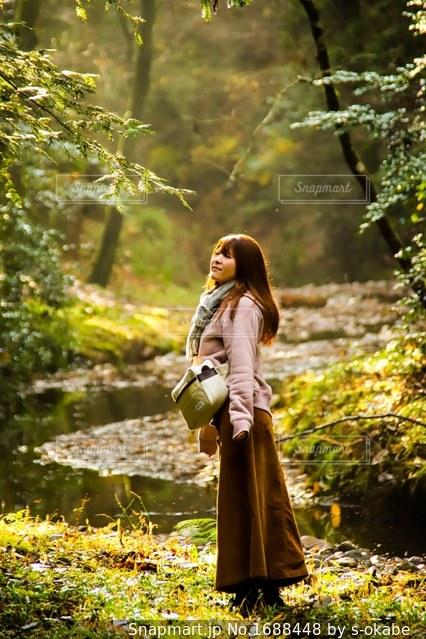 森の横に立っている人の写真・画像素材[1688448]
