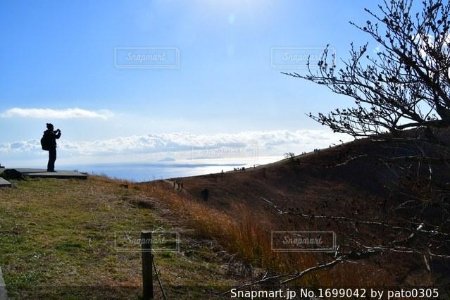 大室山から絶景写真を撮る男性の写真・画像素材[1699042]