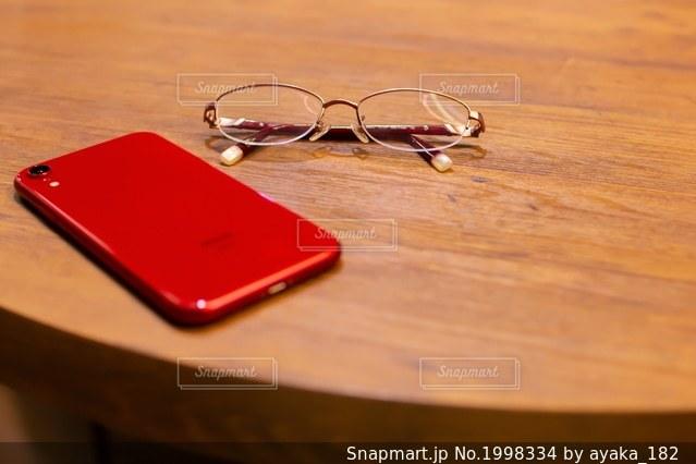 赤い眼鏡とスマホの写真・画像素材[1998334]