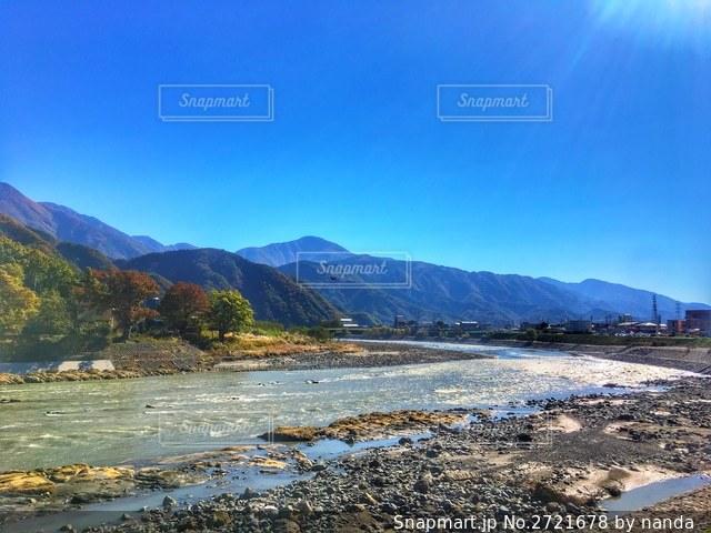 山を背景にした川 ちょっと紅葉の写真・画像素材[2721678]