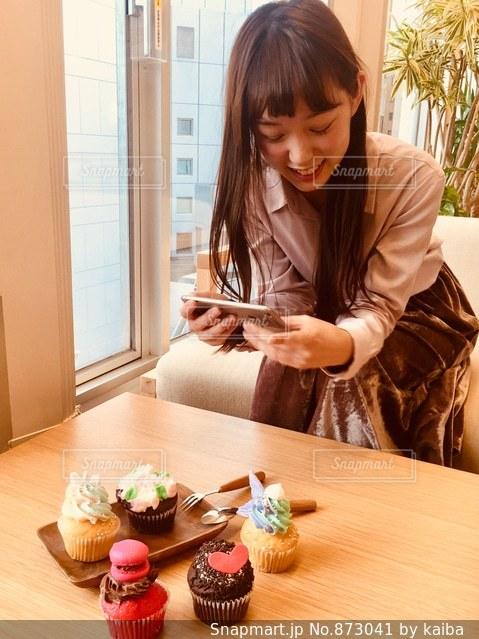 窓の前のテーブルに座っている女性の写真・画像素材[873041]