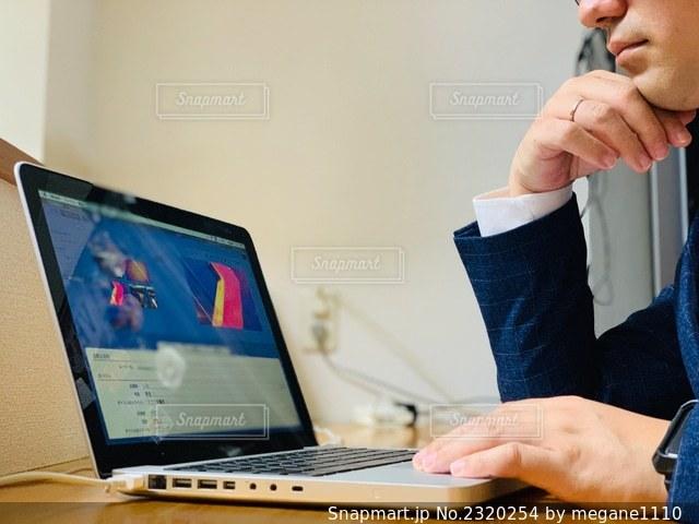 ラップトップコンピュータを使ってテーブルに座っている人の写真・画像素材[2320254]