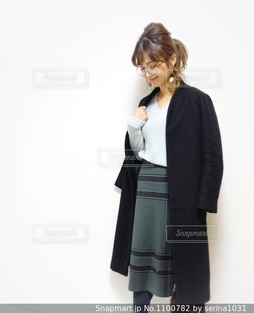 チェックスカートにノーカラーロングコートを肩がけしてうつむきポーズの女性の写真の写真・画像素材[1100782]