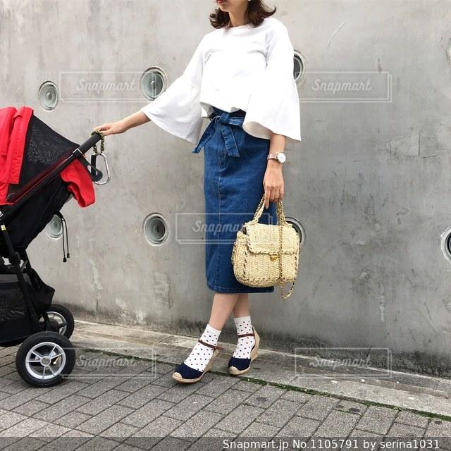 赤いベビーカーを押している女性のコーディネートの写真・画像素材[1105791]