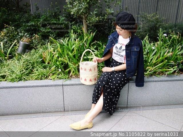 携帯電話で話しているベンチに座っている人の写真・画像素材[1105822]