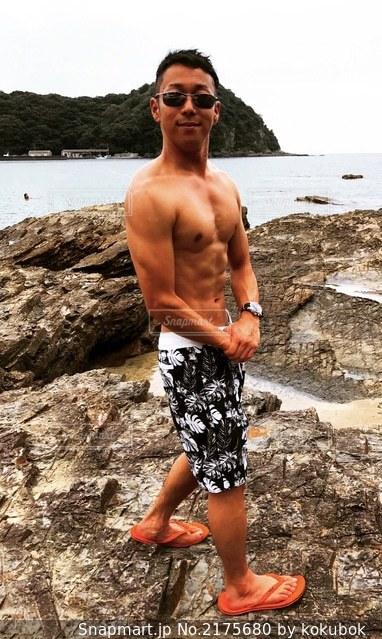 岩場のビーチに立っているマッチョの写真・画像素材[2175680]