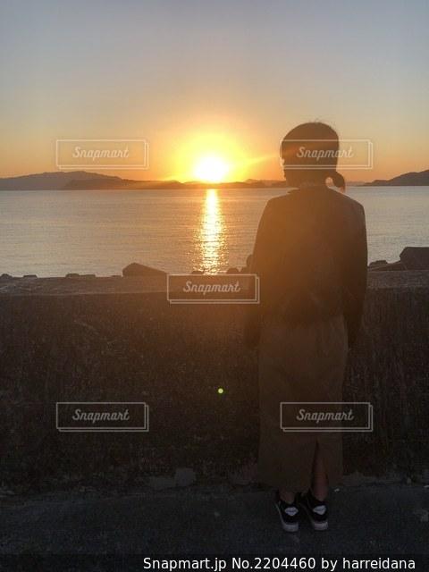 夕日が沈む海辺に立つ女の写真・画像素材[2204460]
