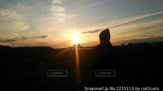 夕焼けの前に立っている人の写真・画像素材[2215113]